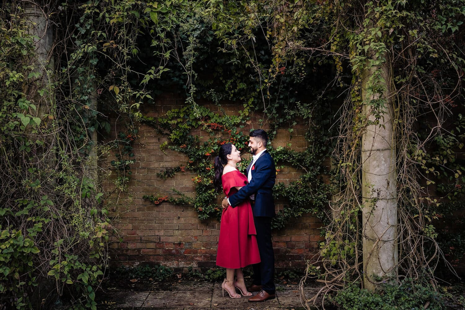 Asian Bride in red dress and groom stand framed by columns at the Hampstead Pergola