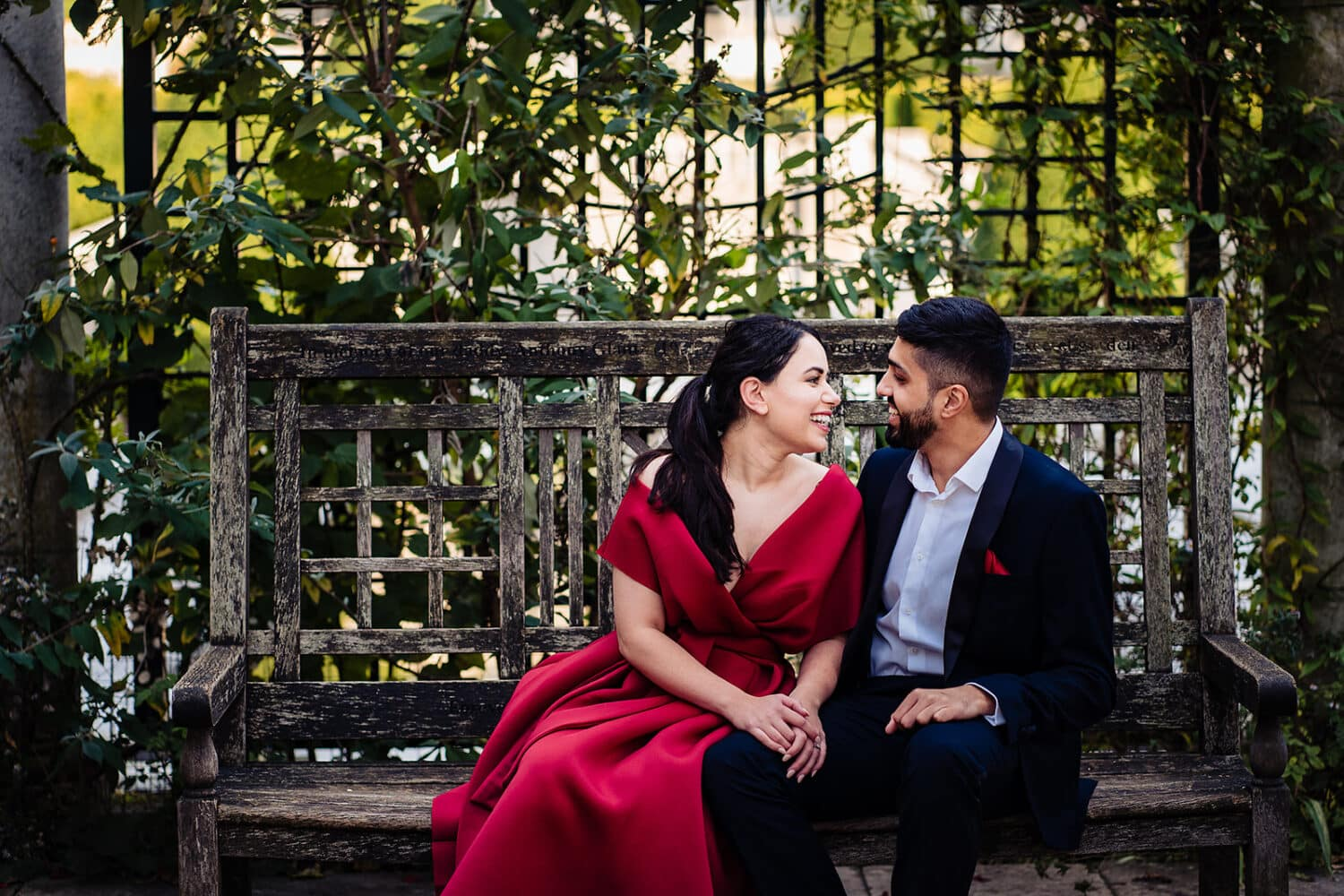Couple laugh sitting on bench at the Hampstead Pergola and Gardens