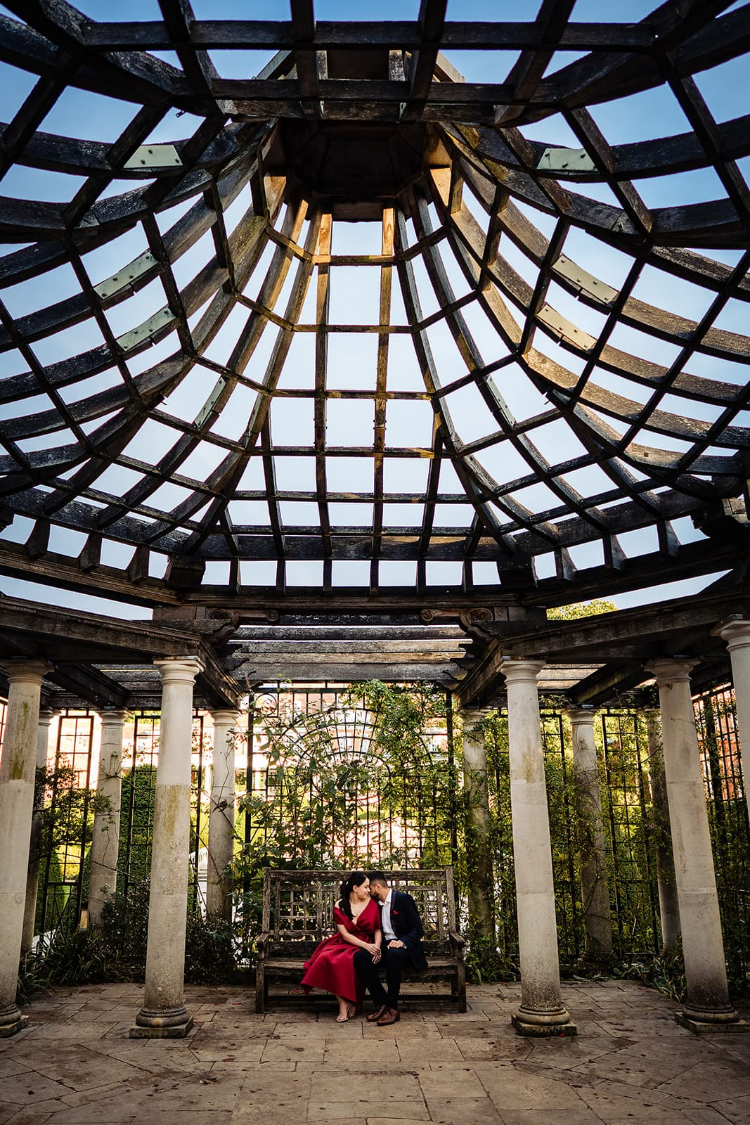 Couple sit on bench and snuggle close below the Hampstead Pergola