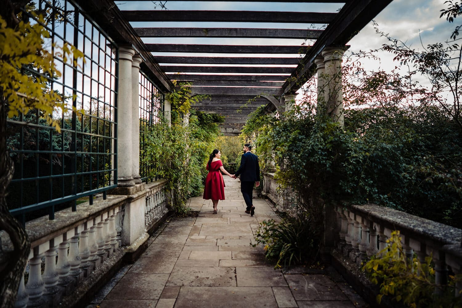 Asian couple walk hand in hand at London's iconic Hampstead Pergola & Gardens
