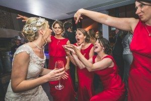 Bride and bridesmaids dancing and singing loudly at their Coworth Park wedding
