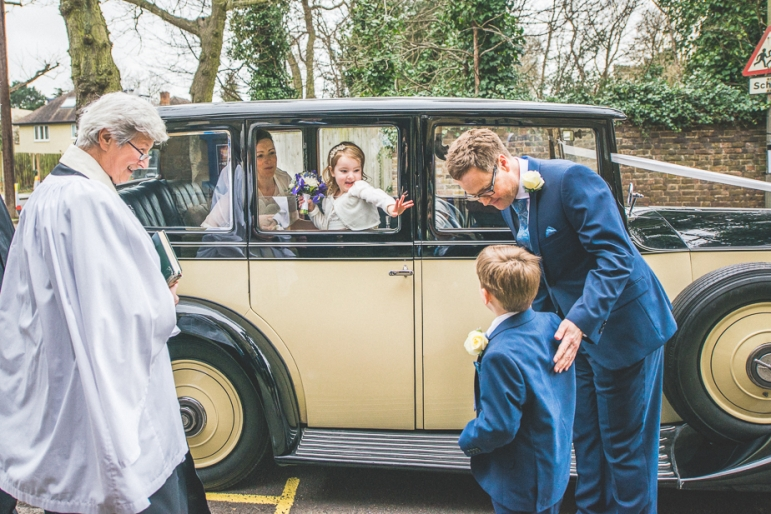 Bride and flower girl arriving in the wedding car and greeting the groom and ring bearer
