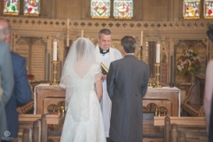 documentary wedding photography of the priest winking at an emotional groom
