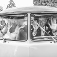 Photo of bride and groom pulling faces in a white VW van