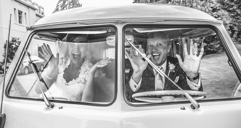 Bride and Groom waving hello from a VW campervan