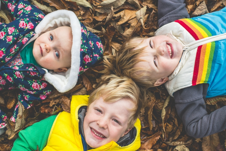 Three children lying in the autumn leaves at Knole Park Sevenoaks Family and Children Photographer