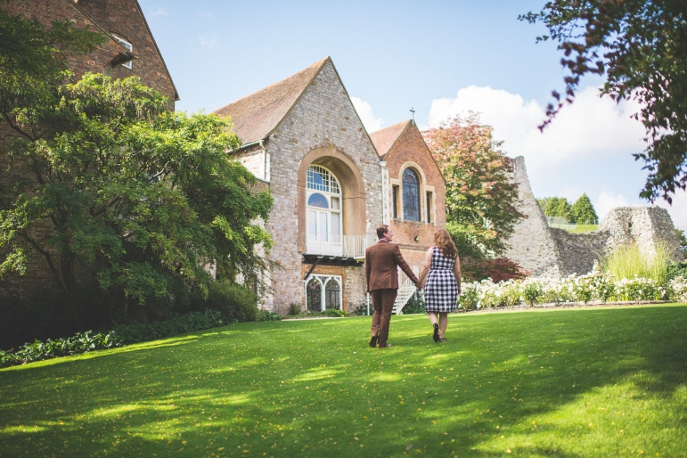 Couple walking at Farnham Castle on their tweed and petticoats pre-wedding shoot in the autumn Farnham Castle Wedding Photography