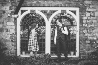 Engaged couple laughing in front of stained glass window of Farnham Castle Bishop