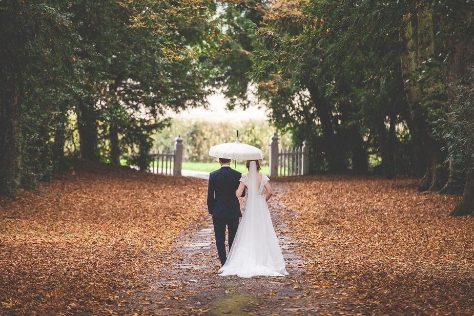 Bride and groom walk through an autumn leaf alley at their Smeetham Hall Barn rustic rainy wedding
