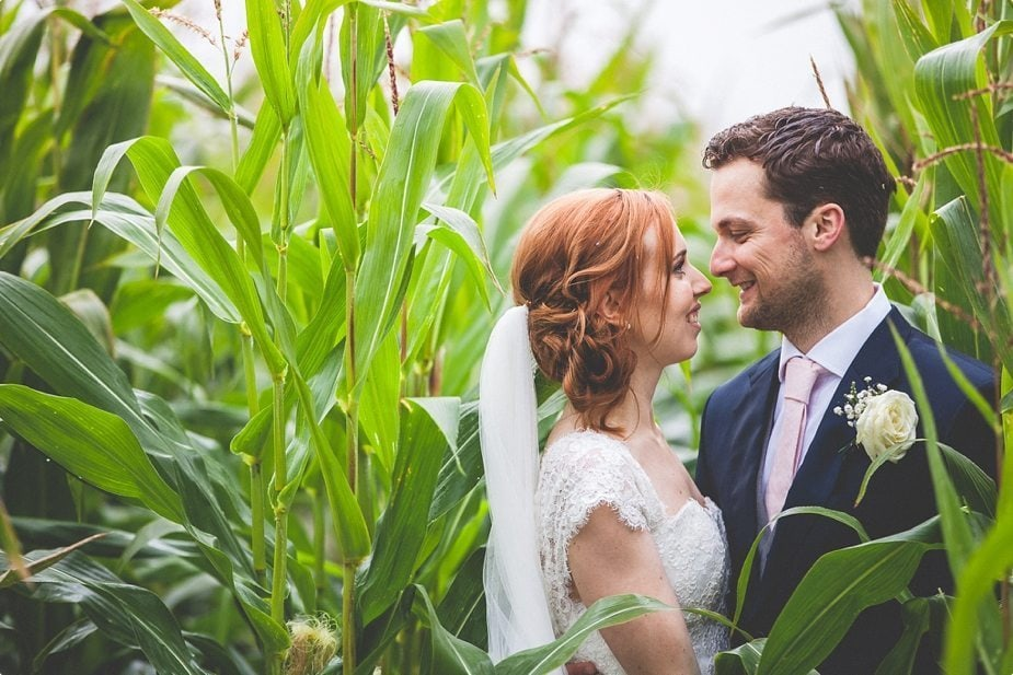 Bride and Groom smile at each other in a corn field at their rustic Smeetham Hall Barn wedding