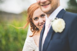 Bride looking past groom's shoulder at their Smeetham Hall Barn rustic rainy wedding