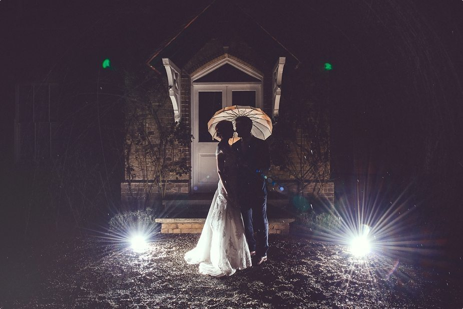 Bride and groom creative light night shot in the rain in front of Smeetham Hall Barn