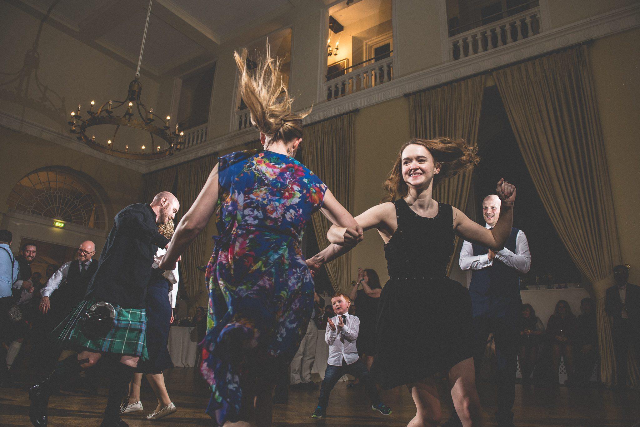 Guests dancing ceilidhs at a fun Farnham Castle wedding