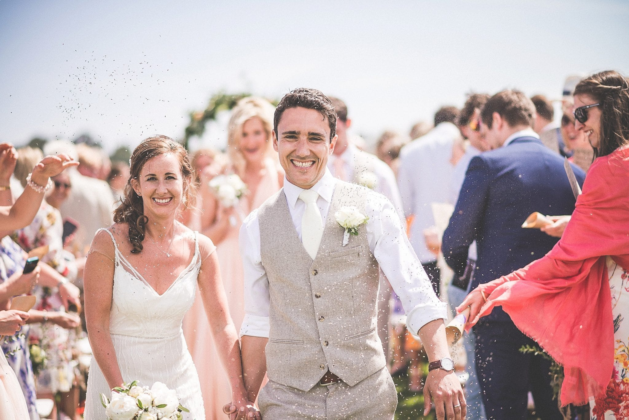 Bride and groom walking down the aisle under a lot of lavender confetti