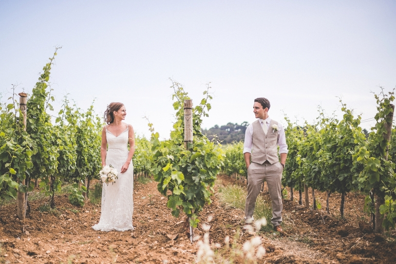 Bride and groom standing in rows of vines at their Domaine de la Croix vineyard South of France Wedding