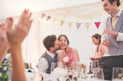 Wedding couple laughing and kissing during the speeches
