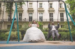 Bride and Groom swinging on swings in the playground at Porchester Hall for their Ethnic Wedding