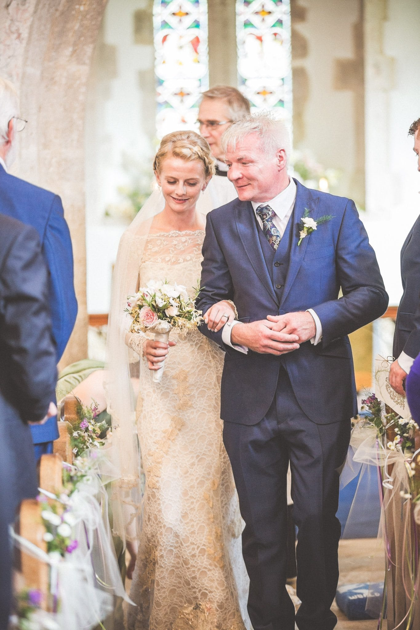 Bride in handmade lace dress walks back down the aisle of the church with her new husband