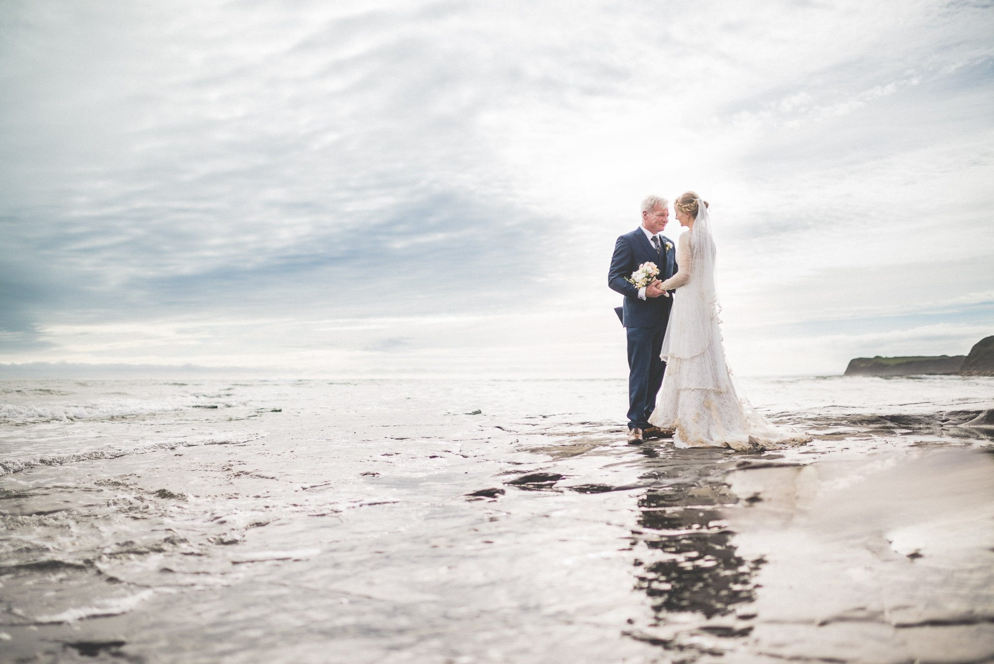 Bride Bea and Groom Jason pose for portrait shots in the waves at Kimmeridge Bay