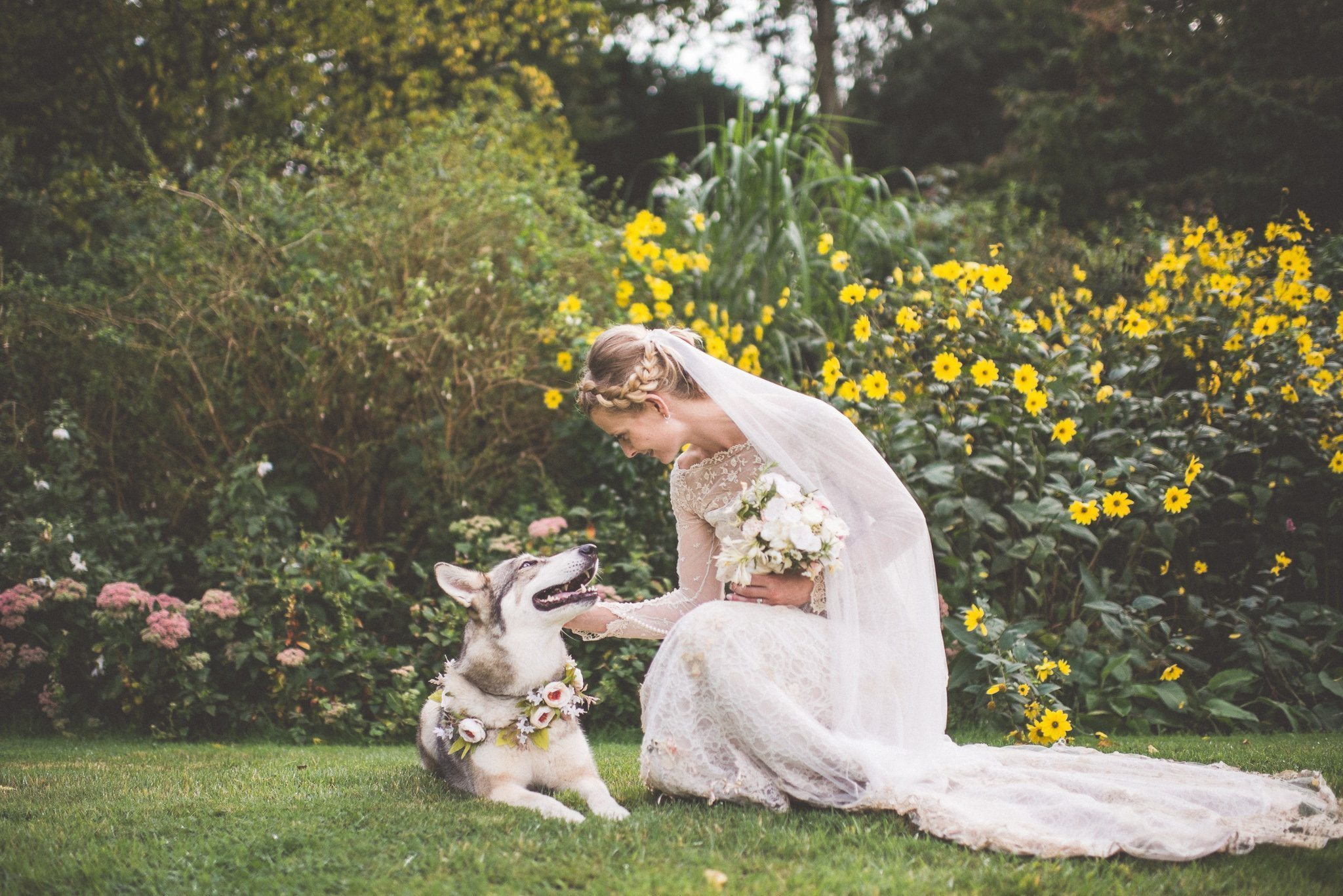 Bride Bea with her dog, who wears a floral collar to match her bouquet