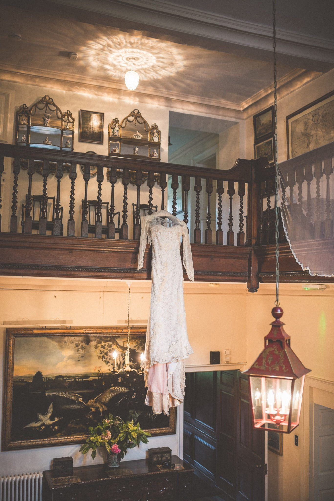 Wedding dress hangs from the staircase at Smedmore House