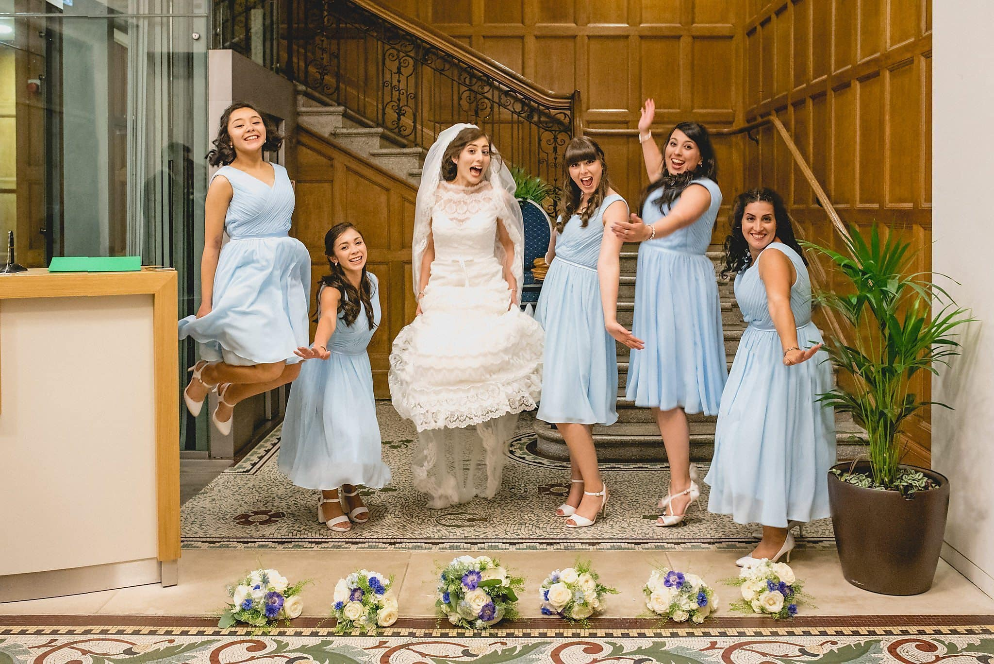 Bride jumping with her bridesmaids at the Royal Horticultural Halls staircase | Start Wedding Planning top tips