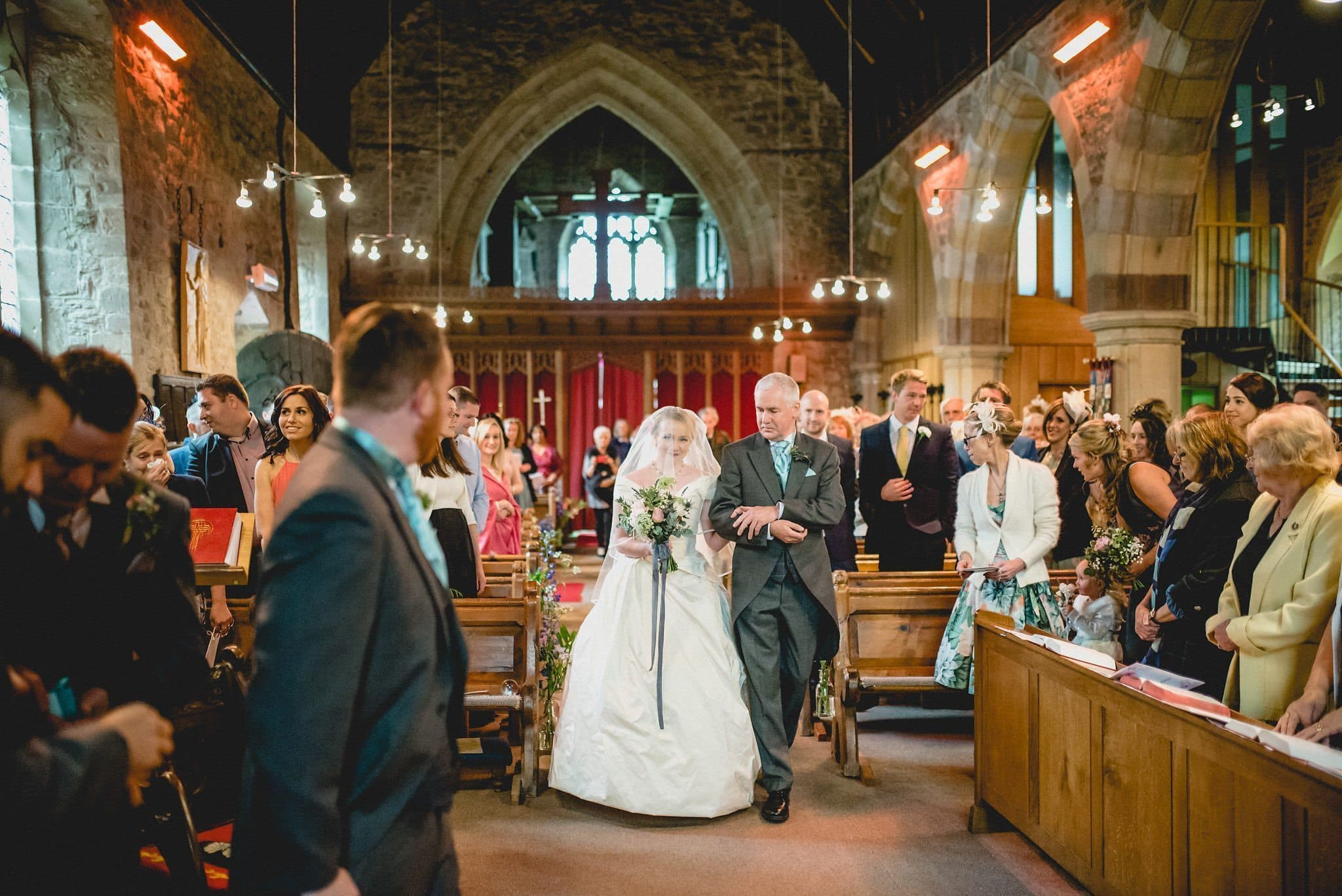 Hatty walks down the aisle on her father's arm, holding her bouquet with a trailing grey ribbon