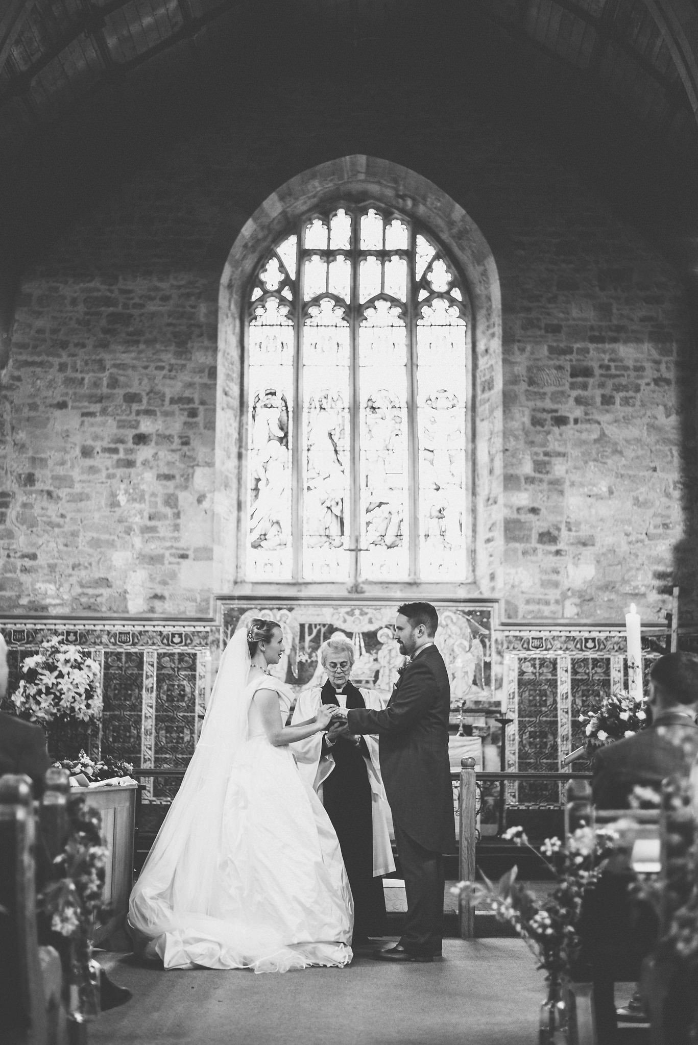 A black and white shot of the couple at the altar, holding hands as they are pronounced man and wife
