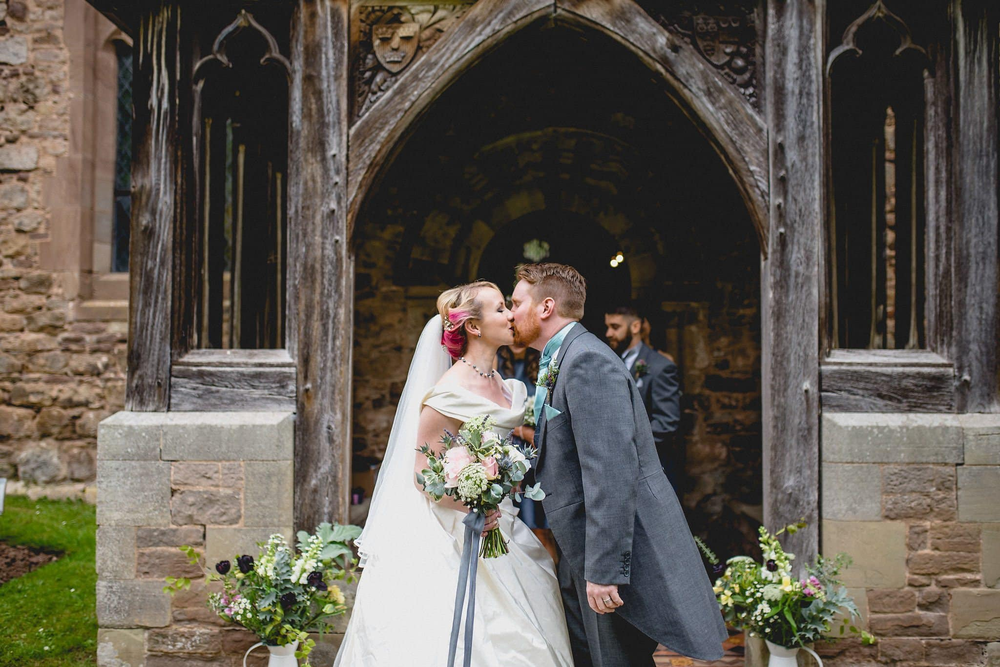 Hatty and Steven kiss outside the church after their wedding ceremony