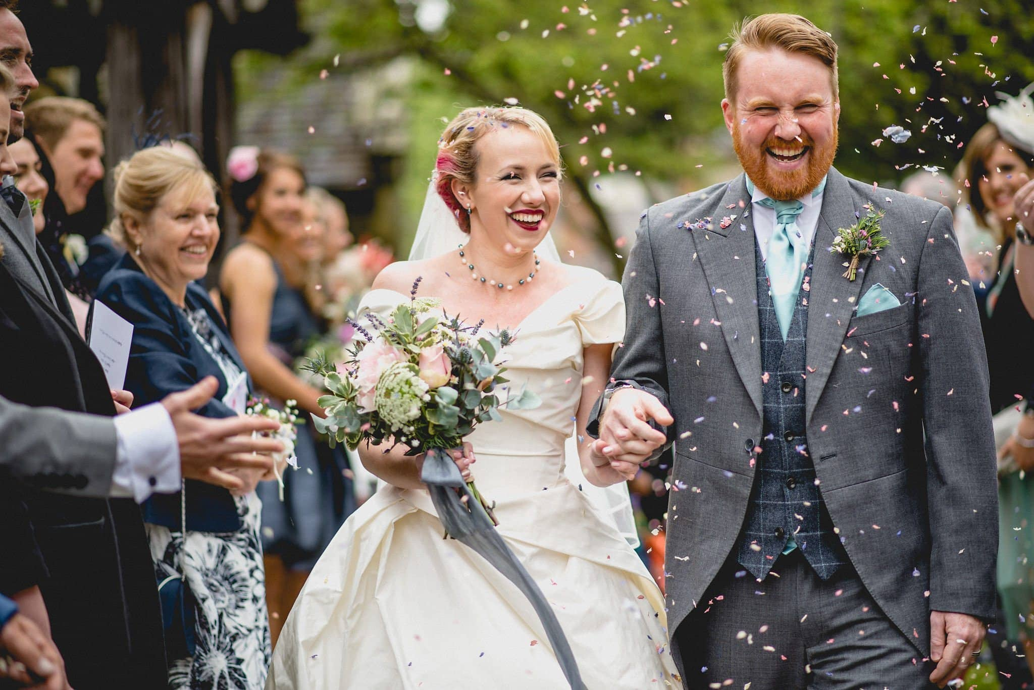 The newlyweds walk through the churchyard in a shower of petal confetti