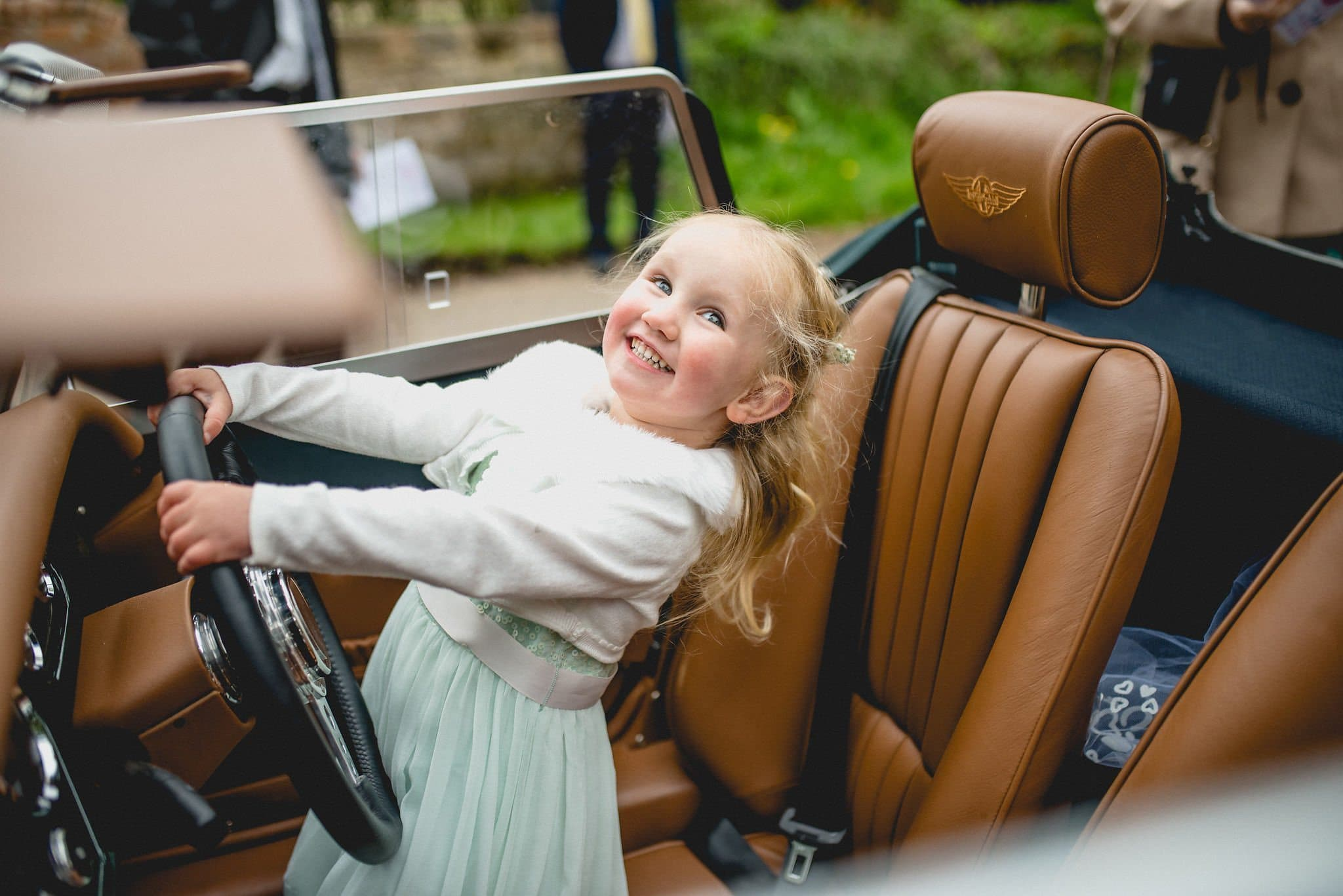 The couple's daughter looks cheeky in her mint green flower girl dress as she pretends to drive the wedding car