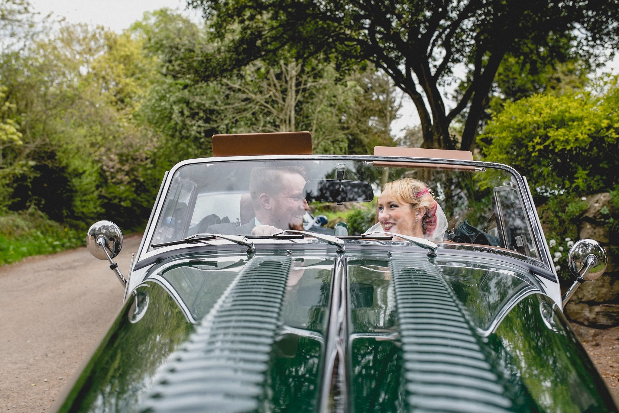Hatty and Steven are seated in the green vintage Morgan, ready to drive from the ceremony to the reception