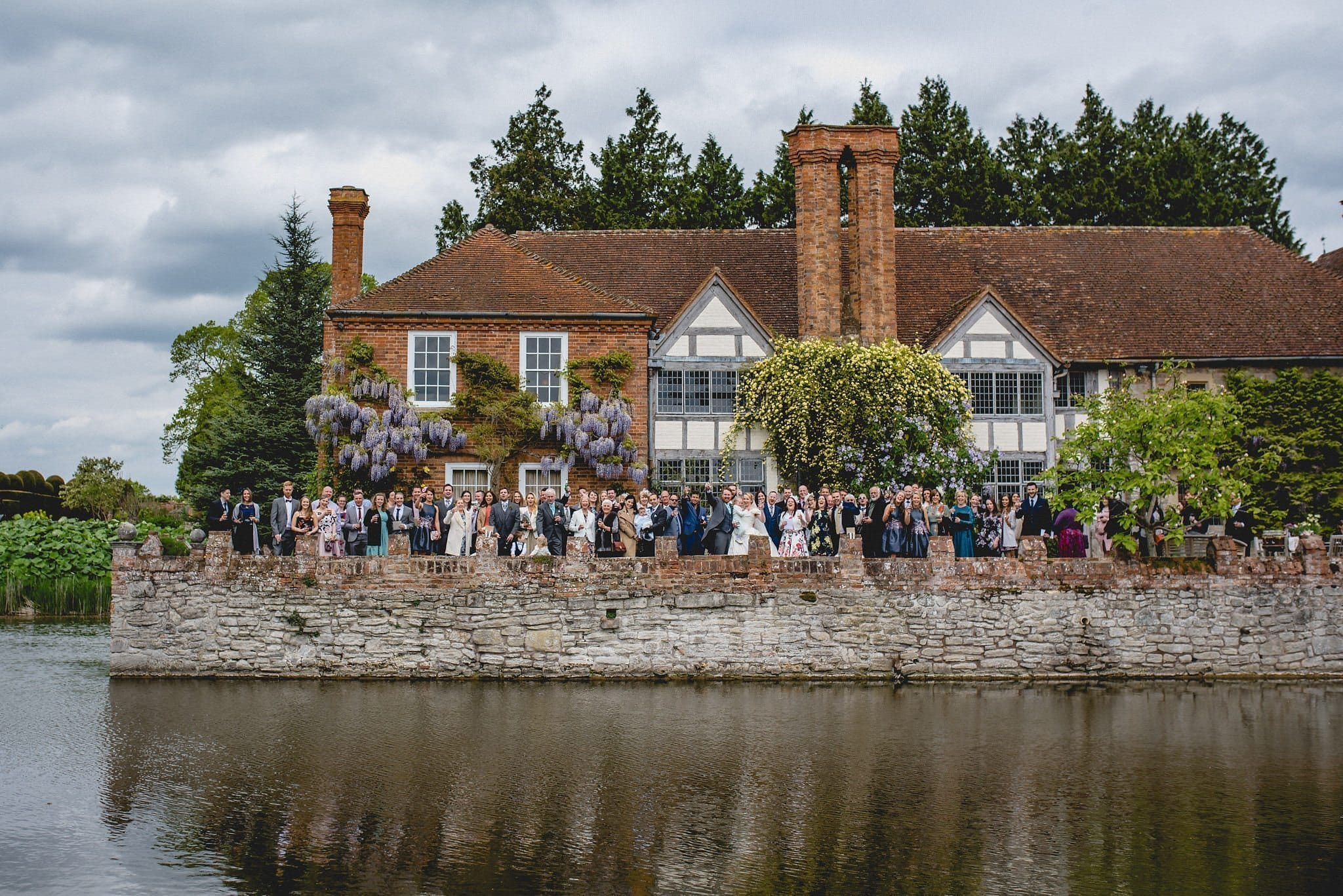 A group shot across the water of all the wedding guests at Birtsmorton Court