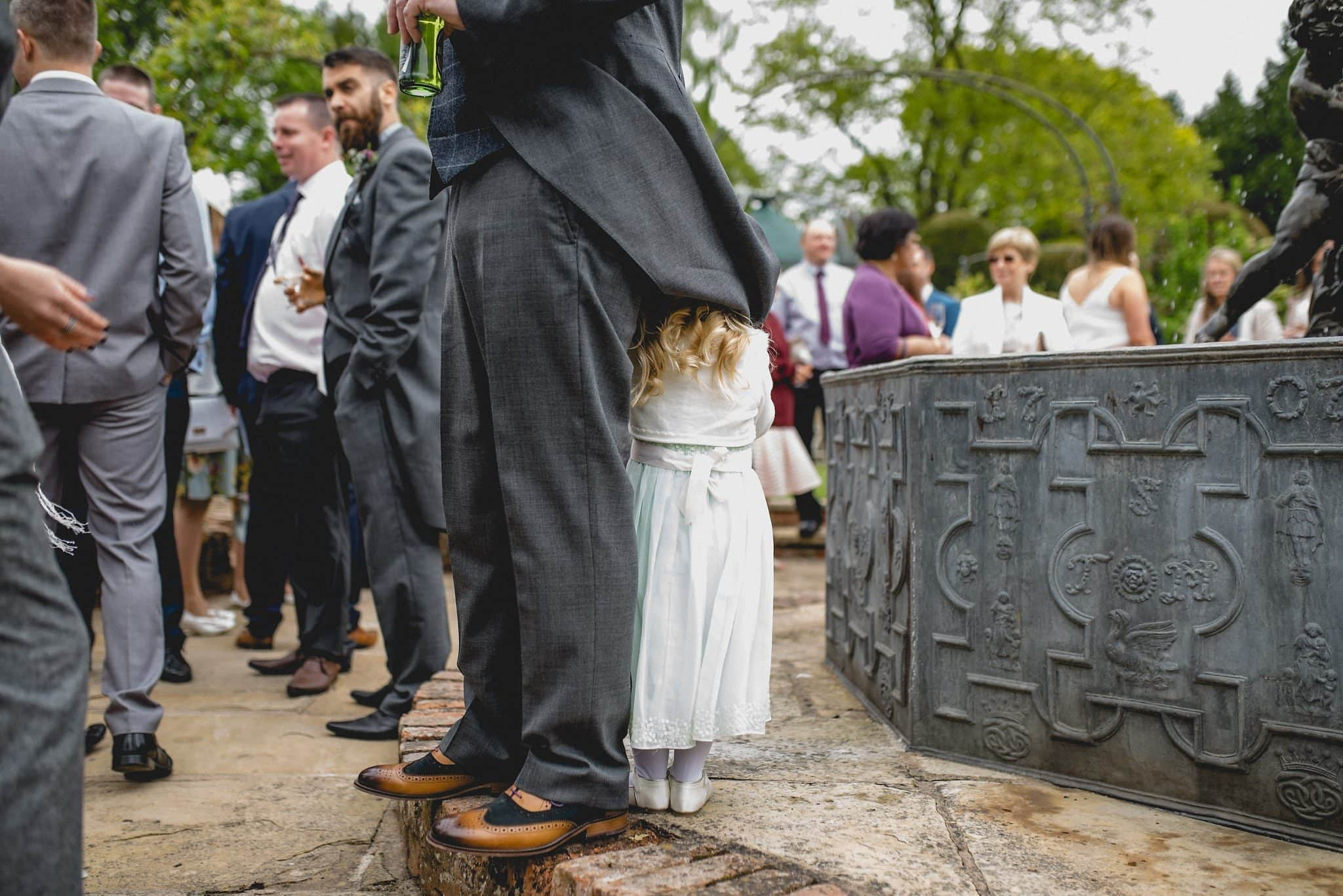 Groom's daughter hiding under his coat tails at his birtsmorton court wedding