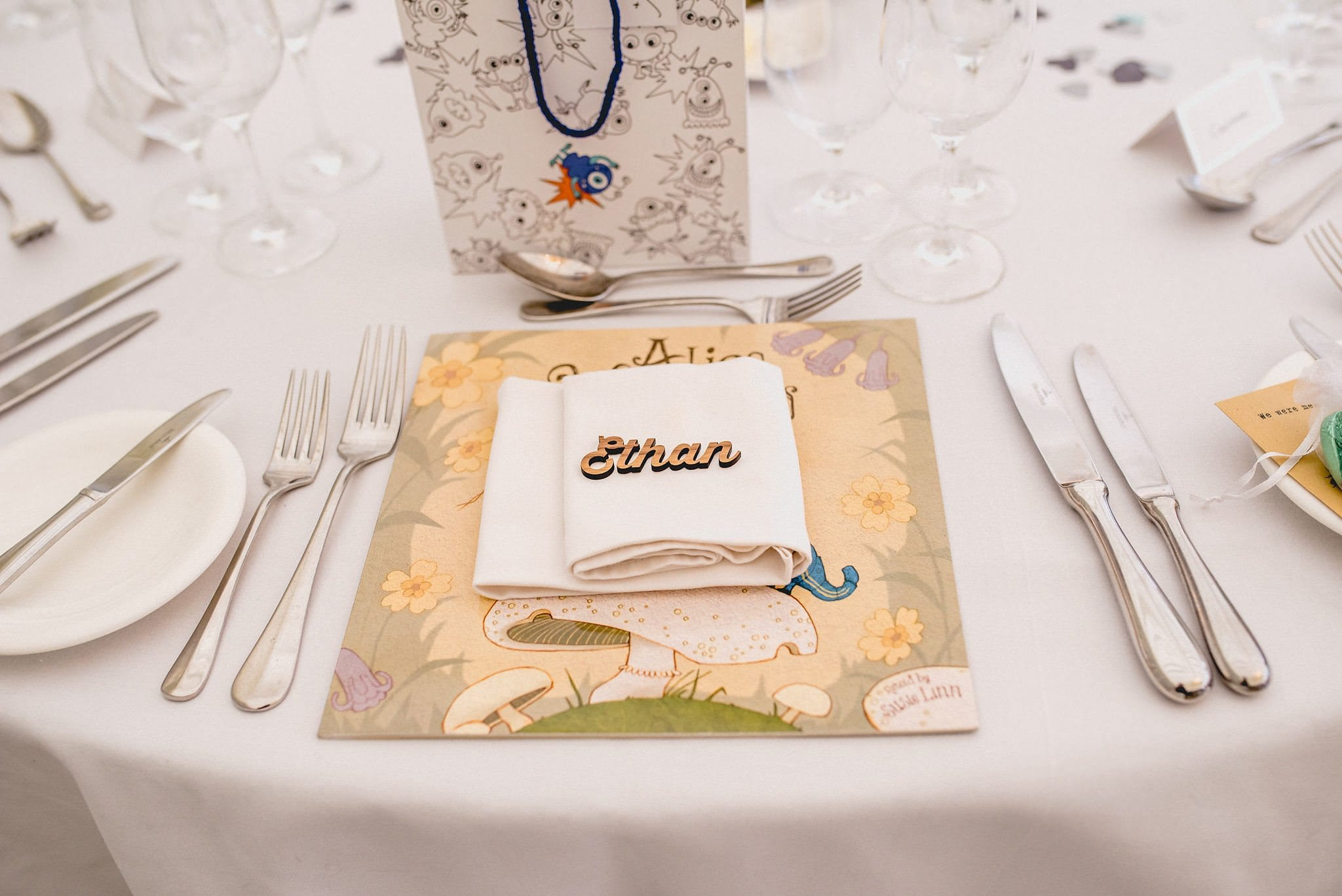 A close up of one of the place settings, featuring a gift bag and a laser cut wooden place name