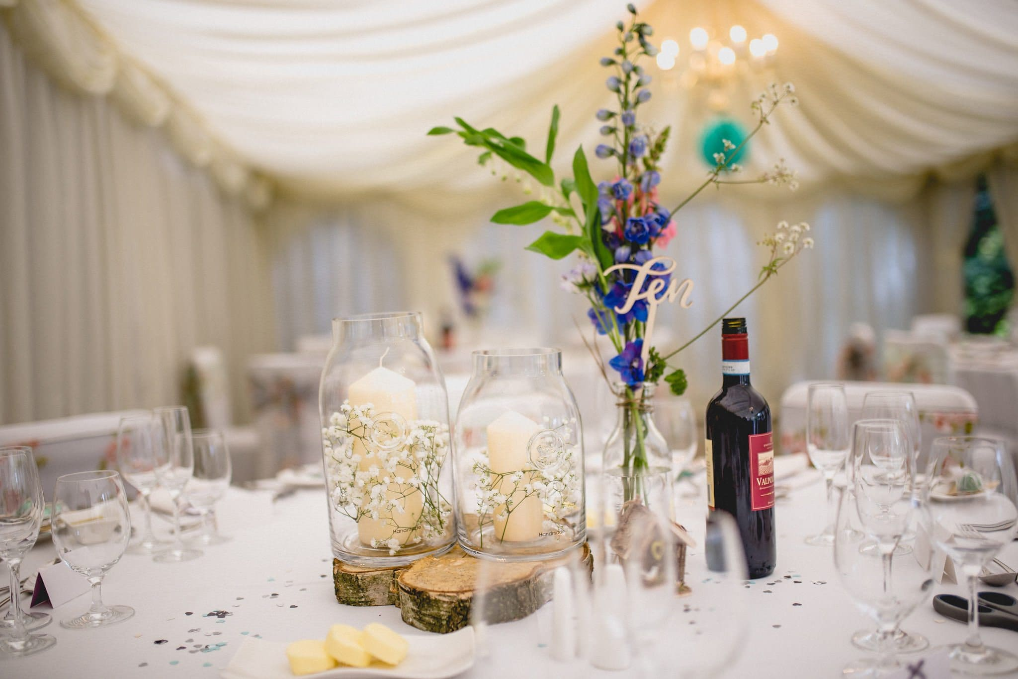 A close up of one of the table centres, with pillar candles and gypsophila, a laser cut table number and wildflowers in a bud vase
