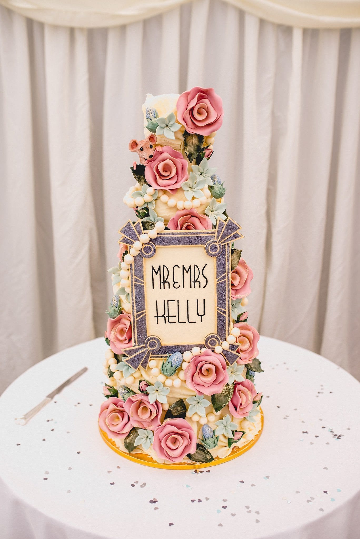 The couple's wedding cake from Choccywoccydoodah, featuring chocolate roses, pearls and a plaque in blue and cream with their married name on it