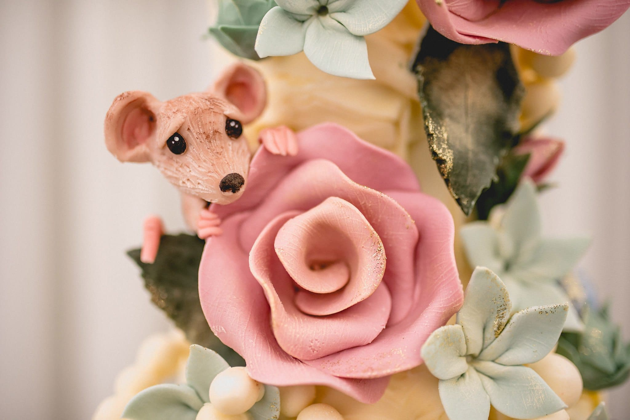 A close up of some of the details on the wedding cake, including a mouse peeping out from behind a rose, all sculpted from chocolate