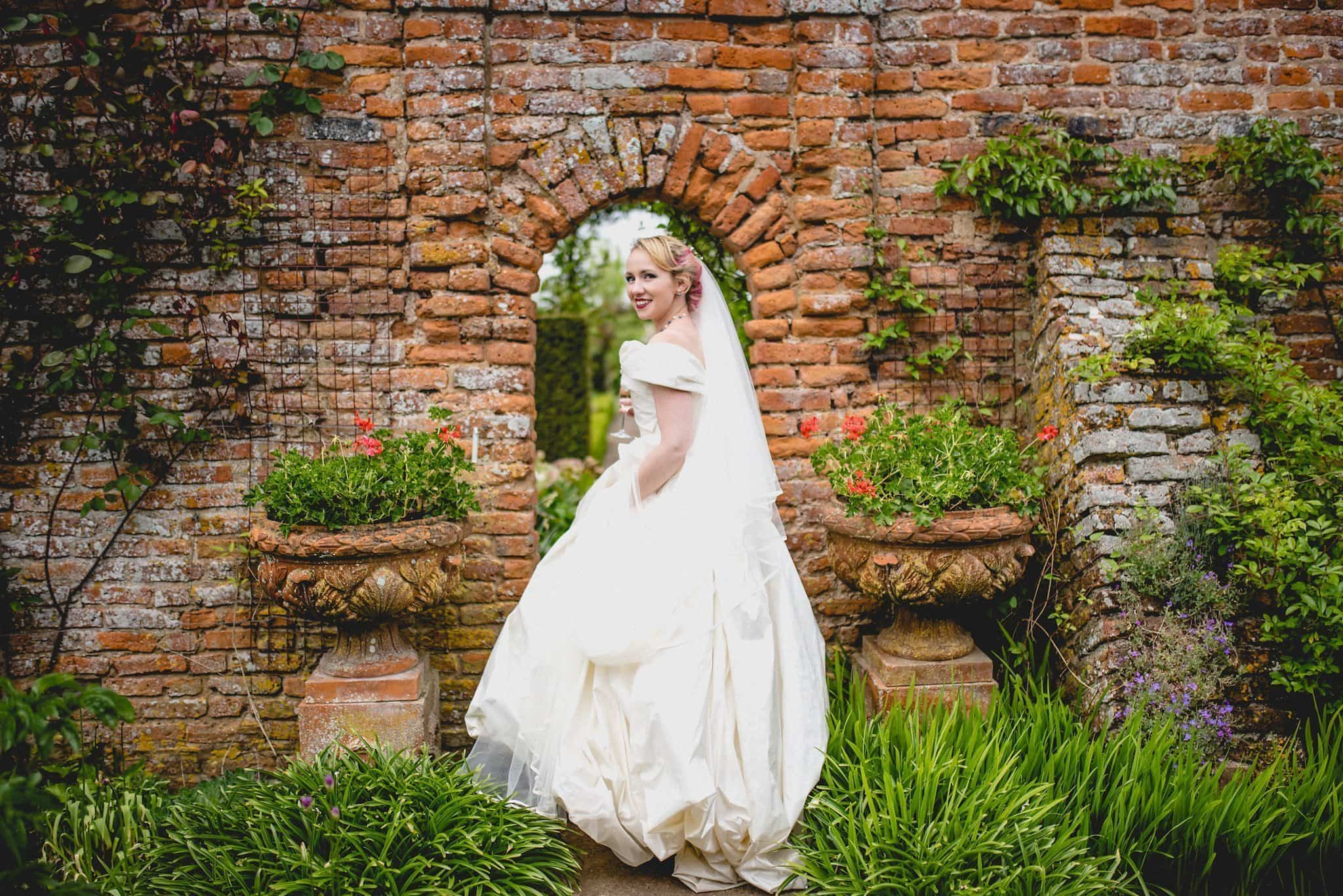 Bride walking through a brick arch at her quirky birtsmorton court wedding