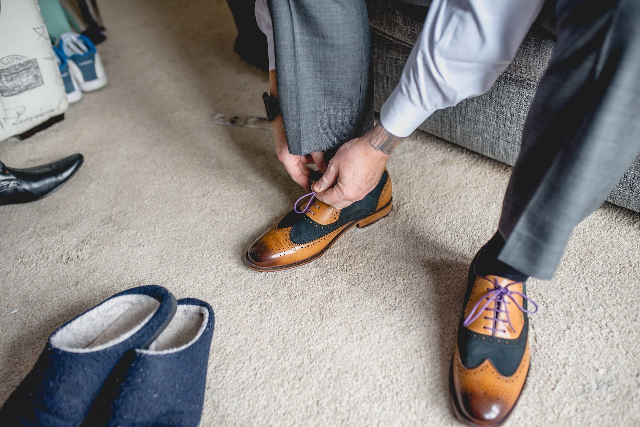 Steven ties his black and tan leather brogues with purple laces