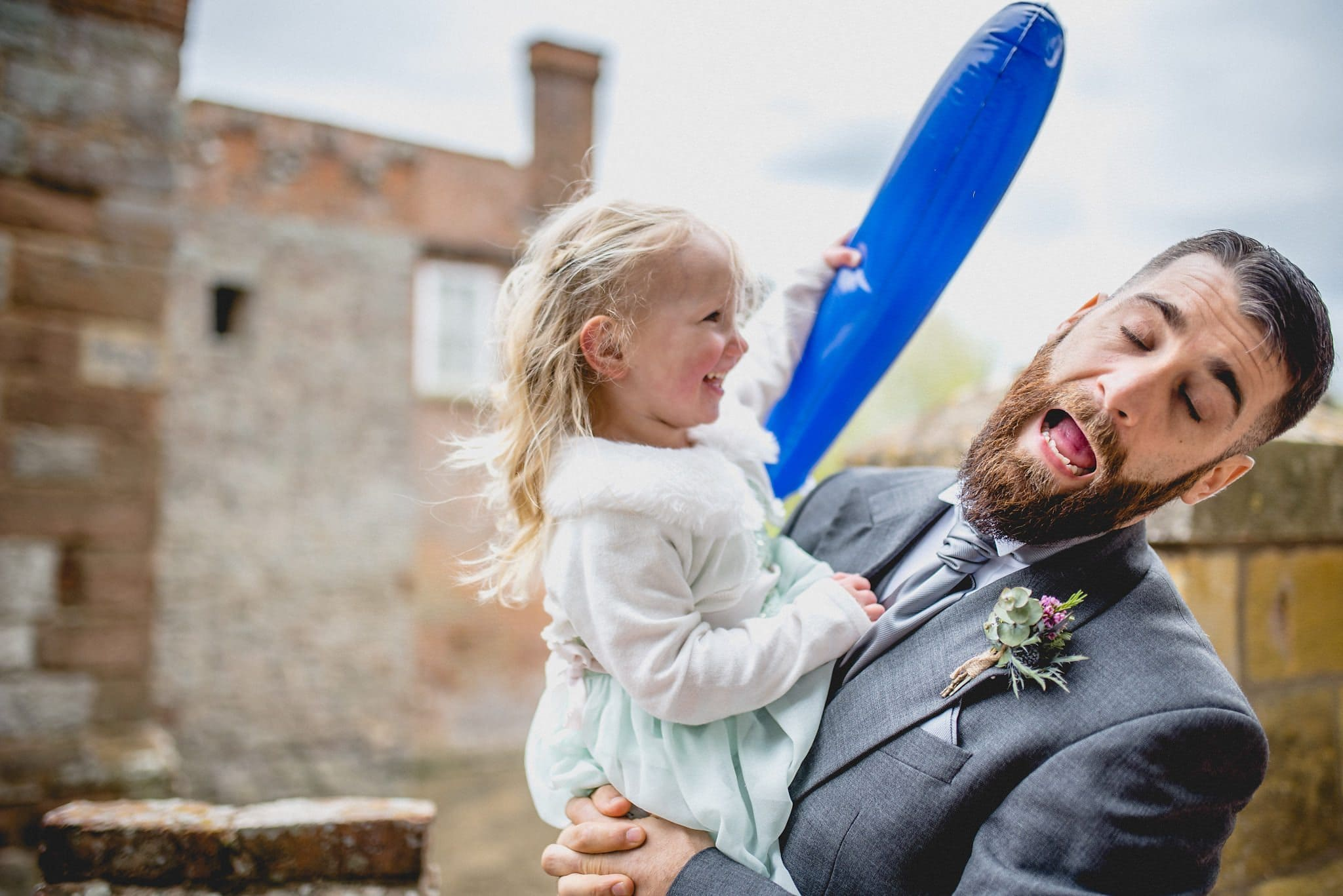 Little girl jokingly hitting a groomsman with a balloon