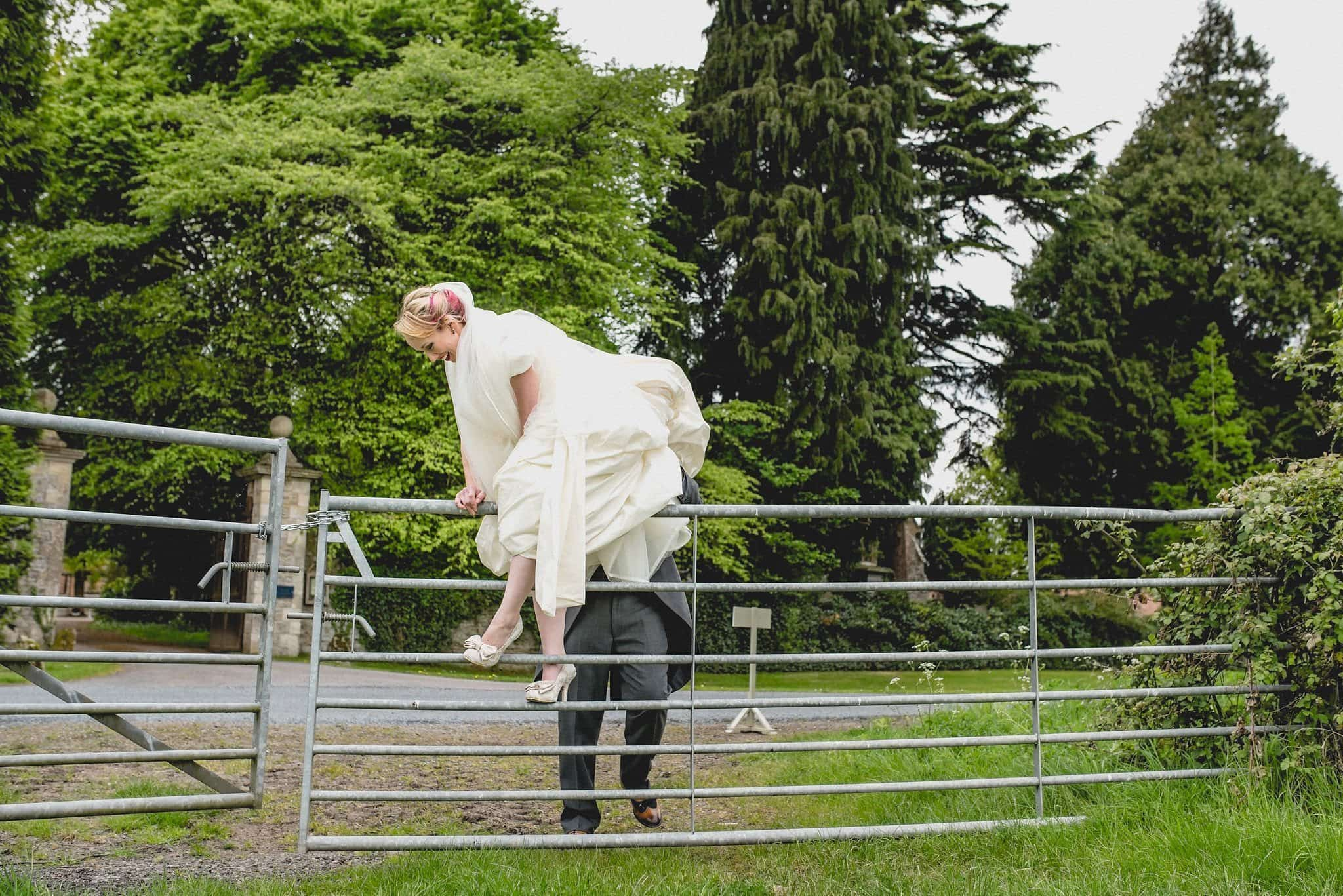 The adventurous bride climbs over a gate in her wedding dress while on their couple's shoot