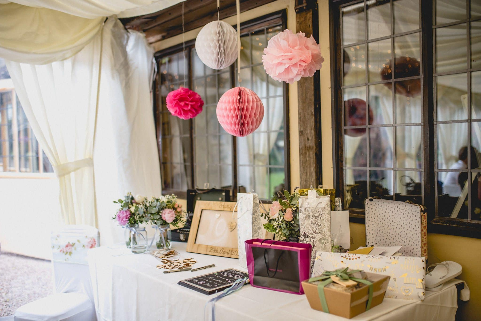 Pom poms and honeycomb balls hang over the guestbook table at Birtsmorton Court