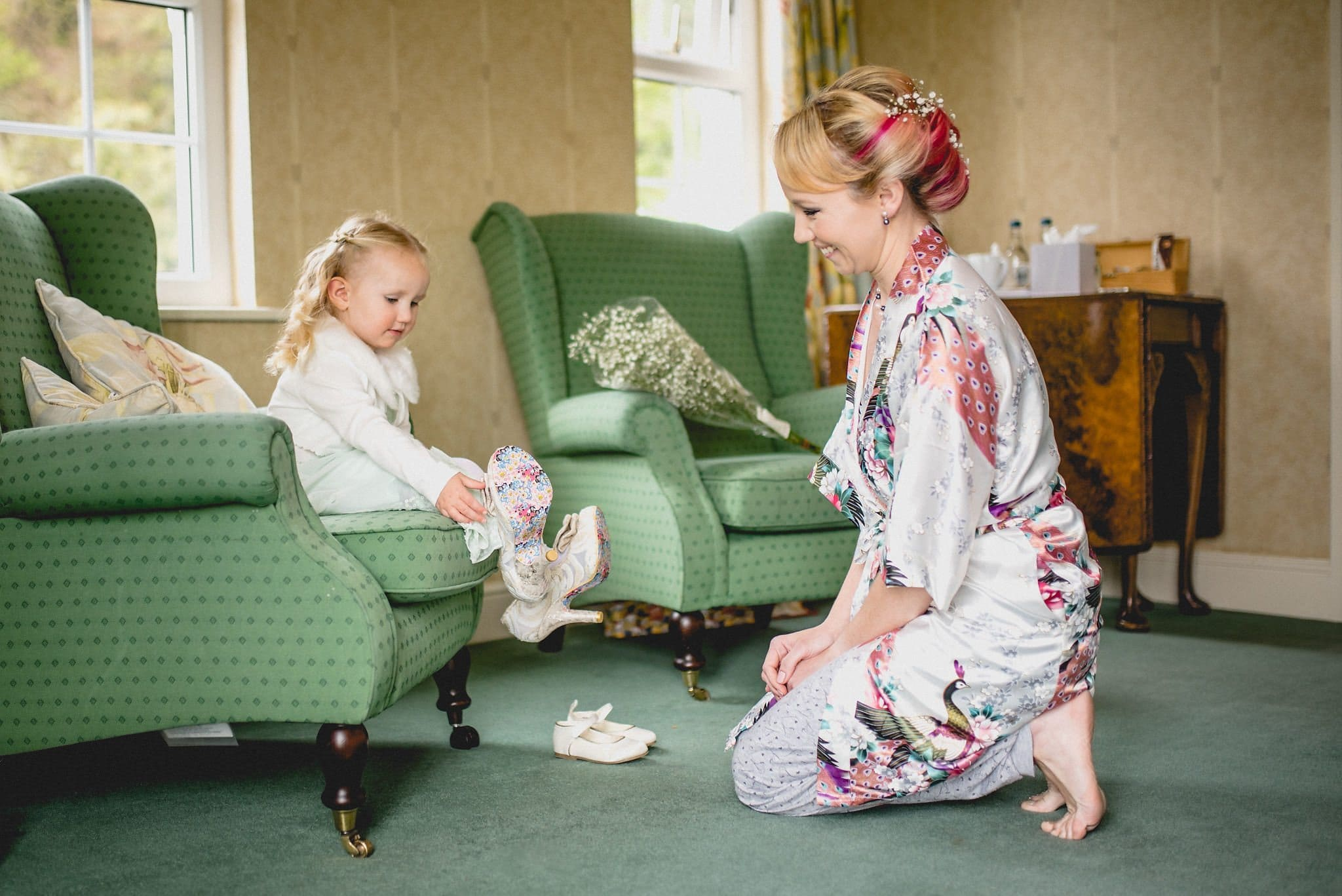 Bride's daughter puts on her mum's bridal shoes prior to her Quirky Birtsmorton Court Wedding