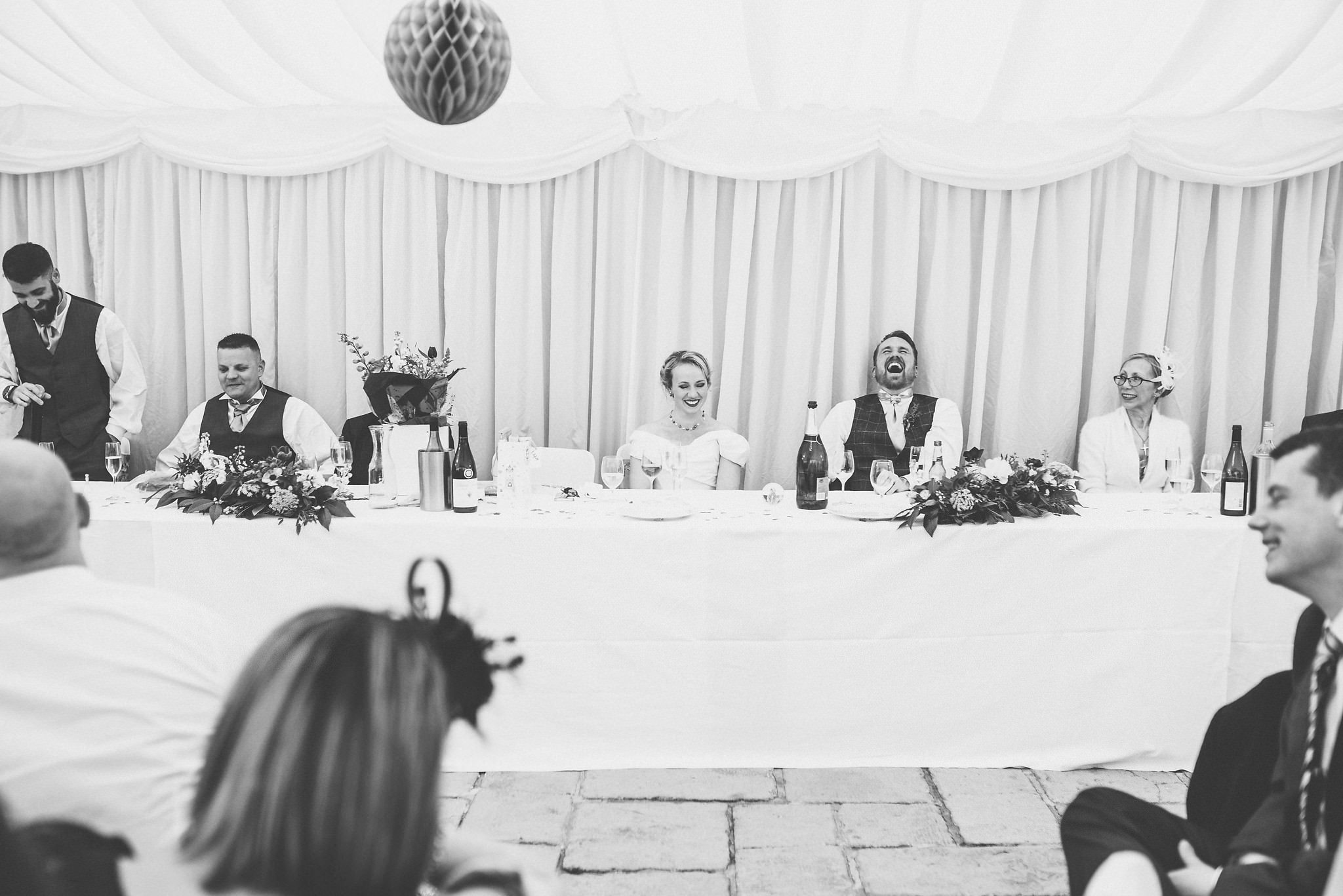 Bride and groom laughing loudly during their speeches at Birtsmorton Court