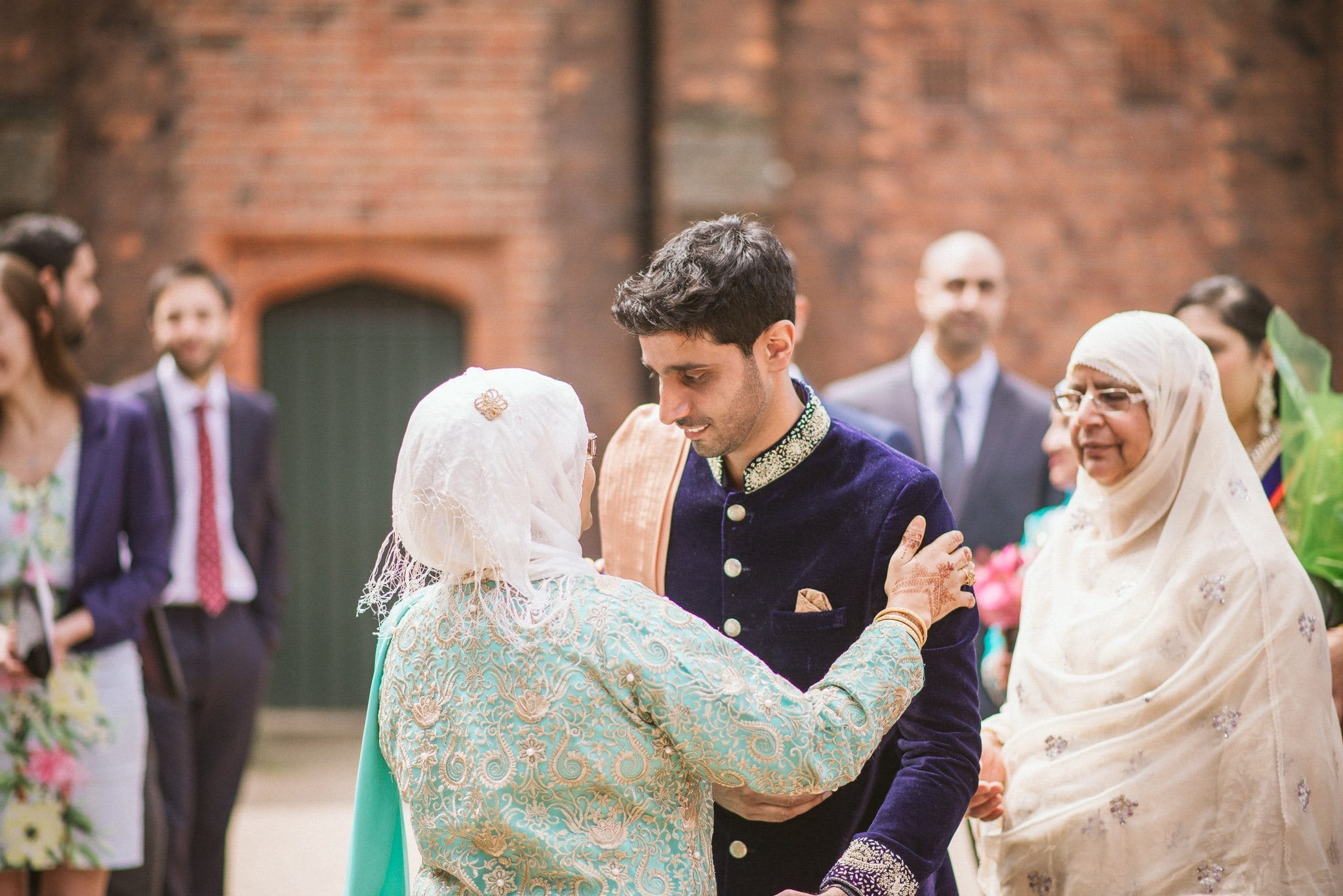 Groom Usman greets guests in the courtyard of Fulham Palace
