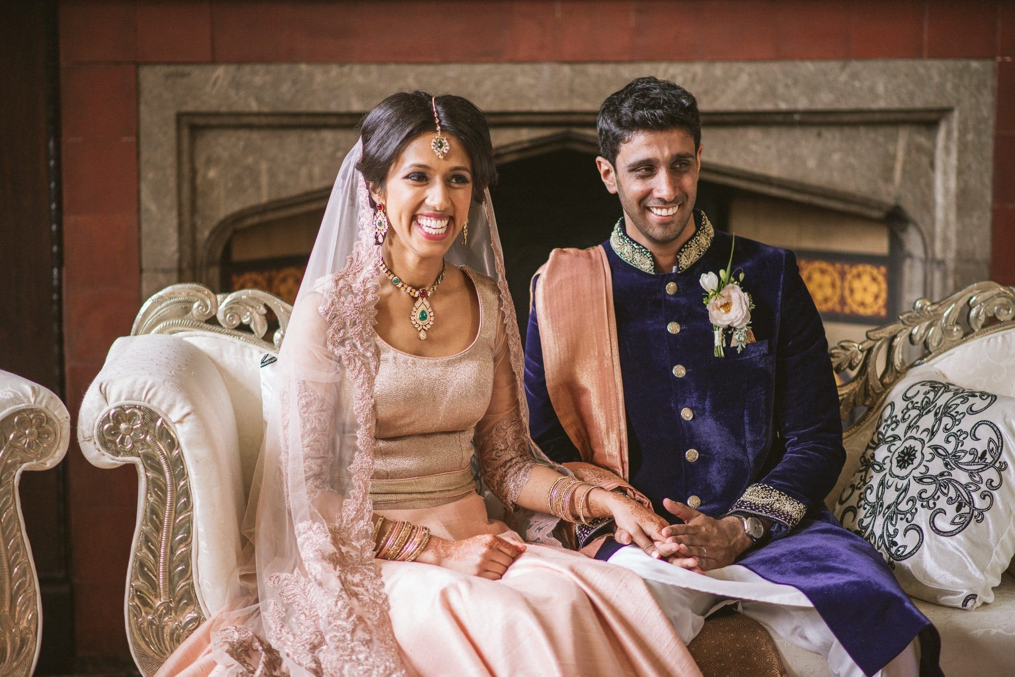 Sorayya and Usman are seated together on a velvet chaise longue during their wedding ceremony