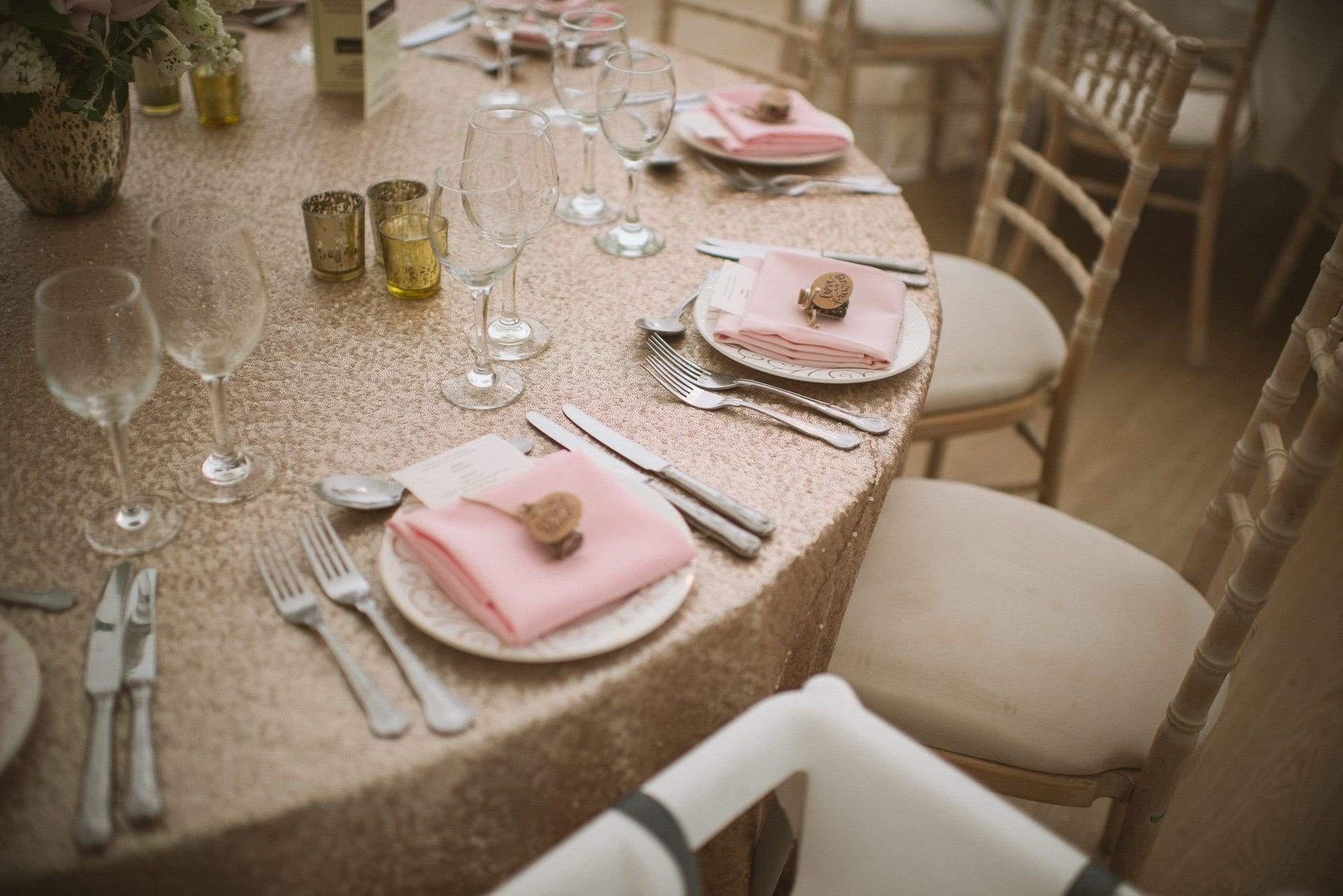 A close up of the tables at Sorayya and Usman's wedding reception, showing gold sequin tablecloth and pale pink napkins.