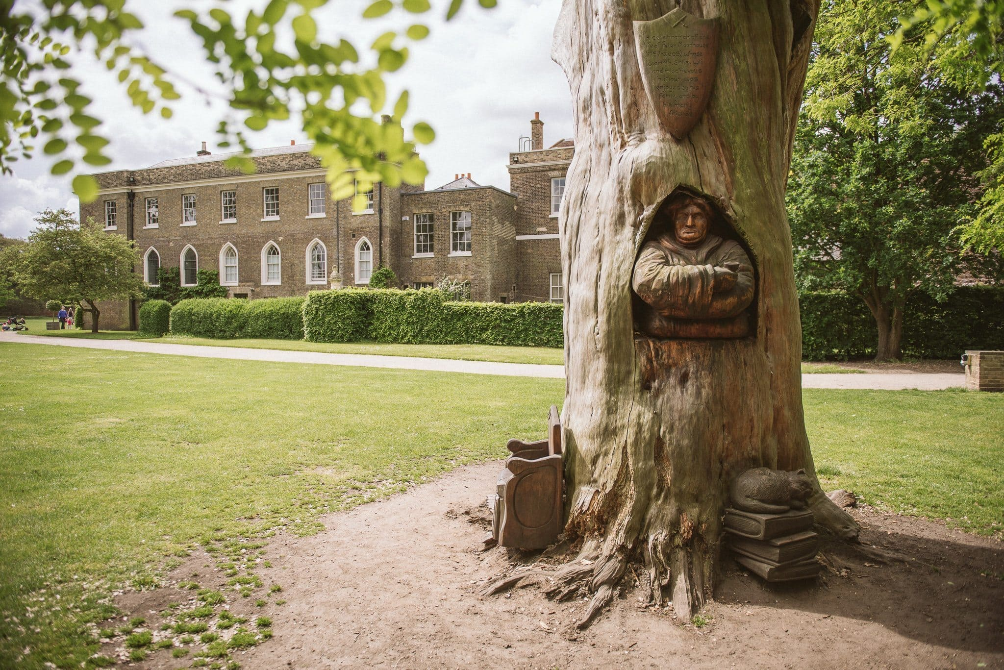 A statue is carved into the trunk of a tree in the grounds of Fulham Palace