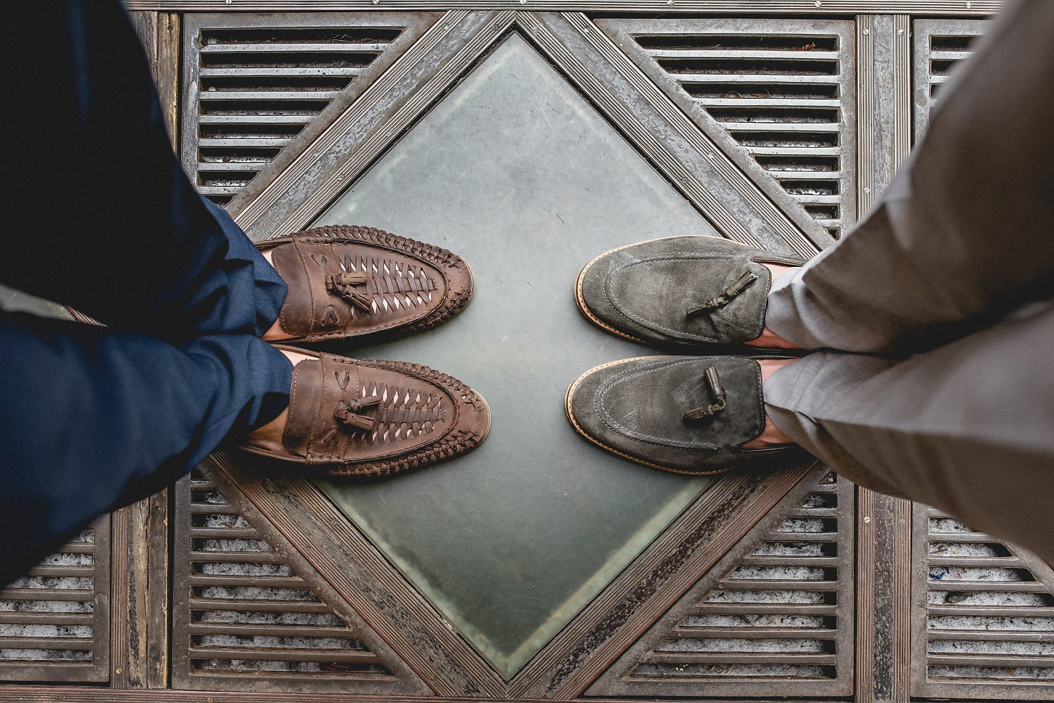 A shot from above showing Drew and Tom's loafers as they face each other on a stylish diamond-patterned terrace
